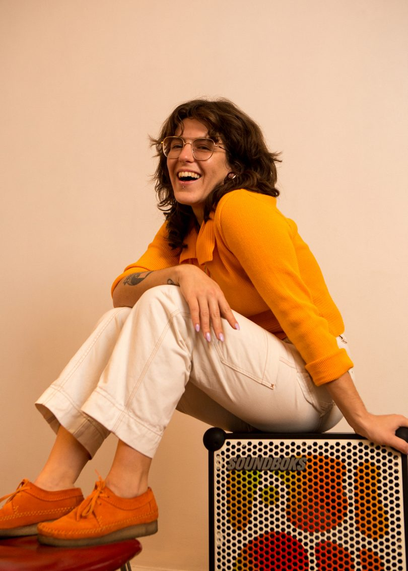 light skinned woman with dark hair and glasses sitting on box and smiling