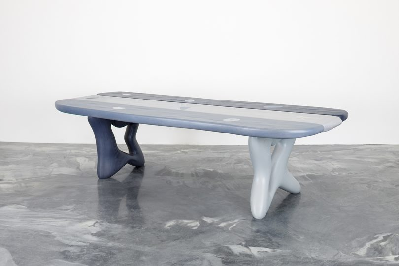 angled abstract table on concrete floor in front of white wall