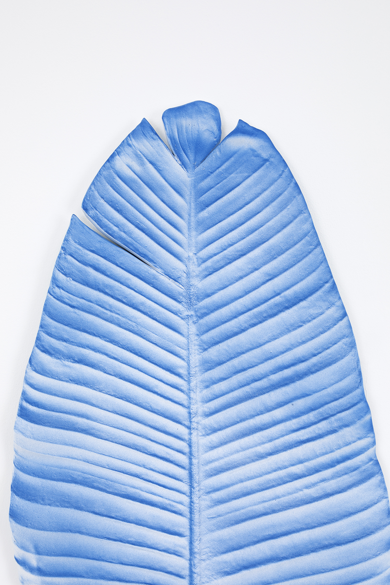 detail of blue leaf sculpture hanging on white wall