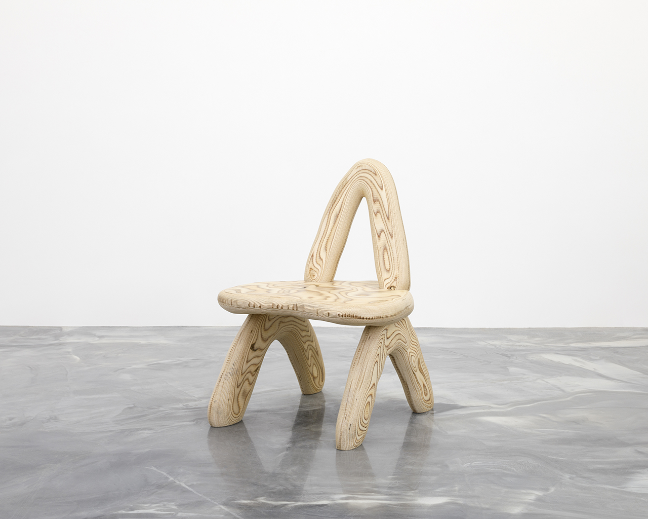 curvaceous wooden chair on concrete floor in front of white wall