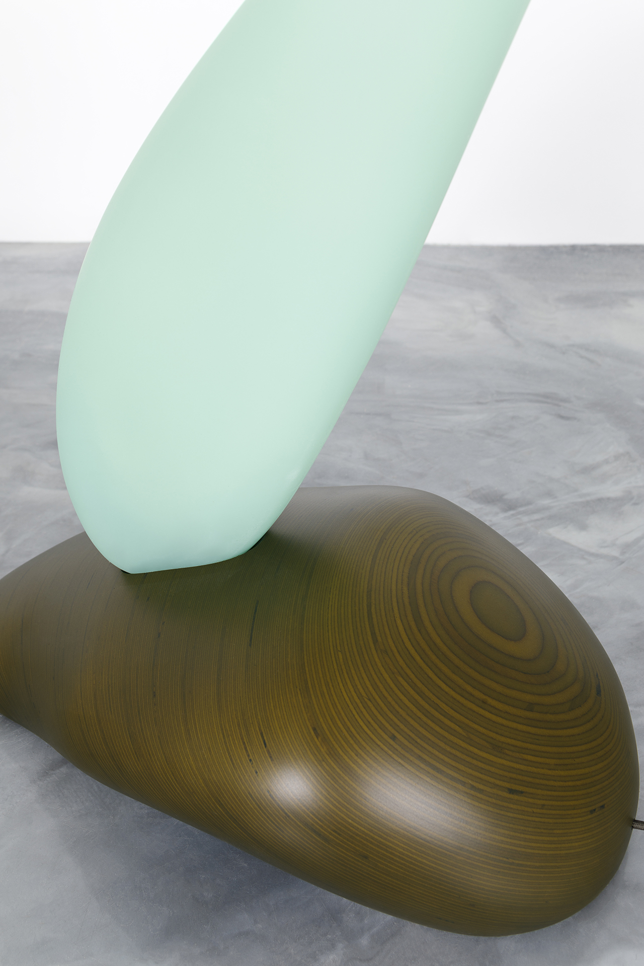 detail of curvaceous abstract floor lamp on concrete floor in front of white wall