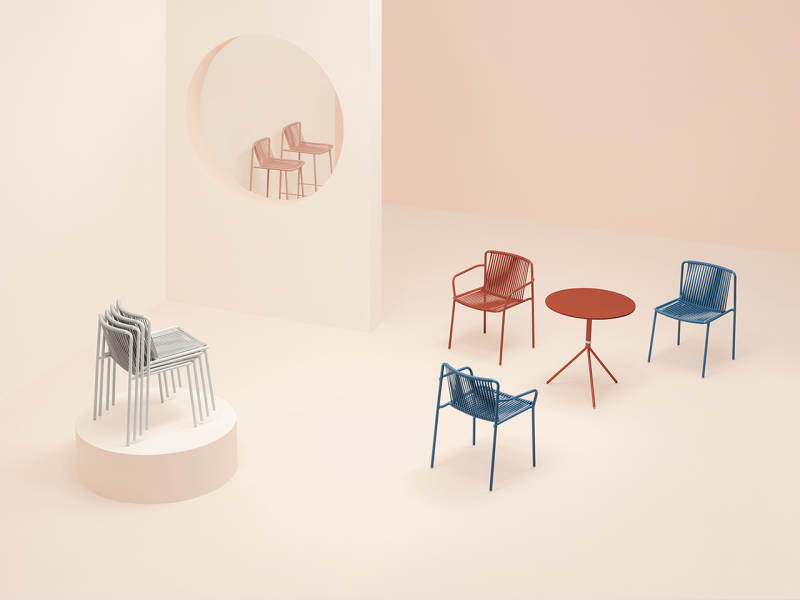 various colored chairs and red bistro table