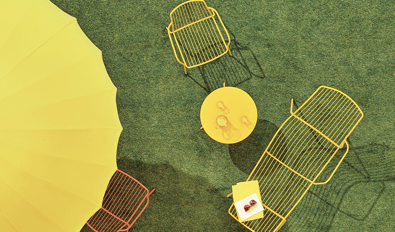 overhead shot of yellow umbrella, bistro table, armchair, and chaise lounge on grass
