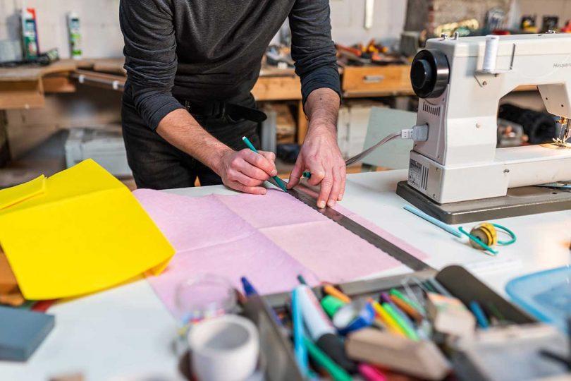 designer marking pink fabric with ruler