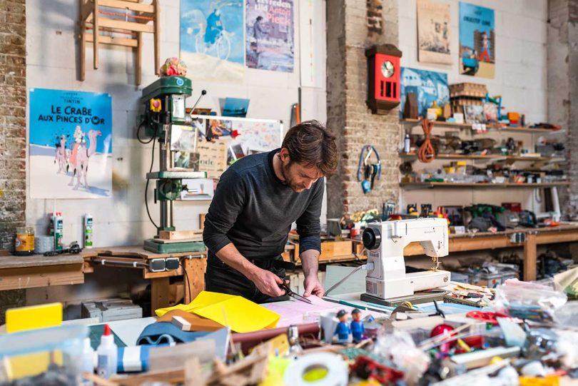 Designer cutting fabric in studio