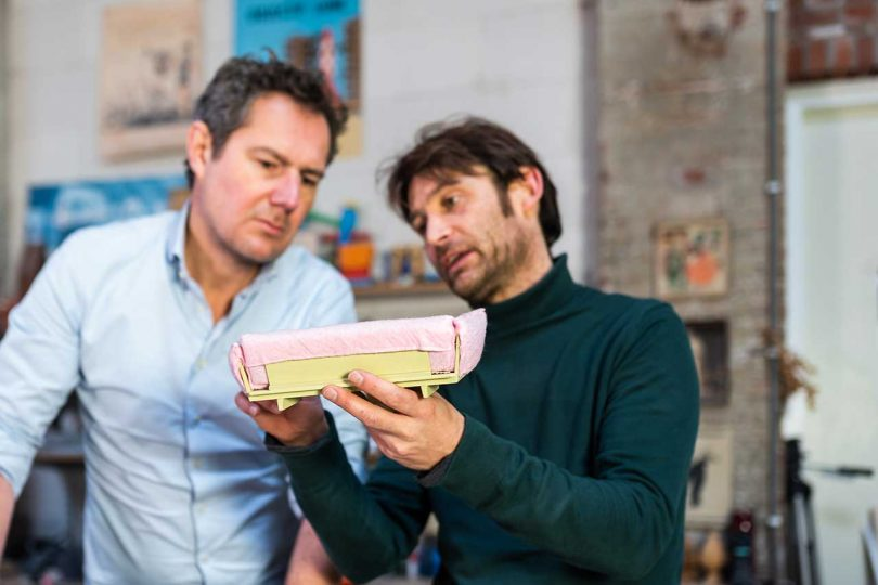 two men looking at miniature sofa prototype