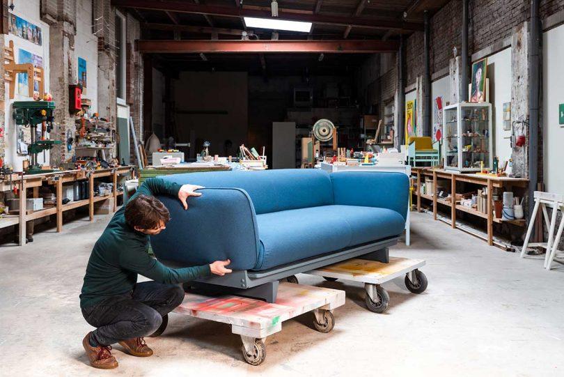Man squatting next to blue sofa on cart