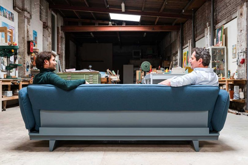 back of blue sofa with two men sitting on it