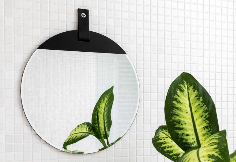 round wall mirror with black tab