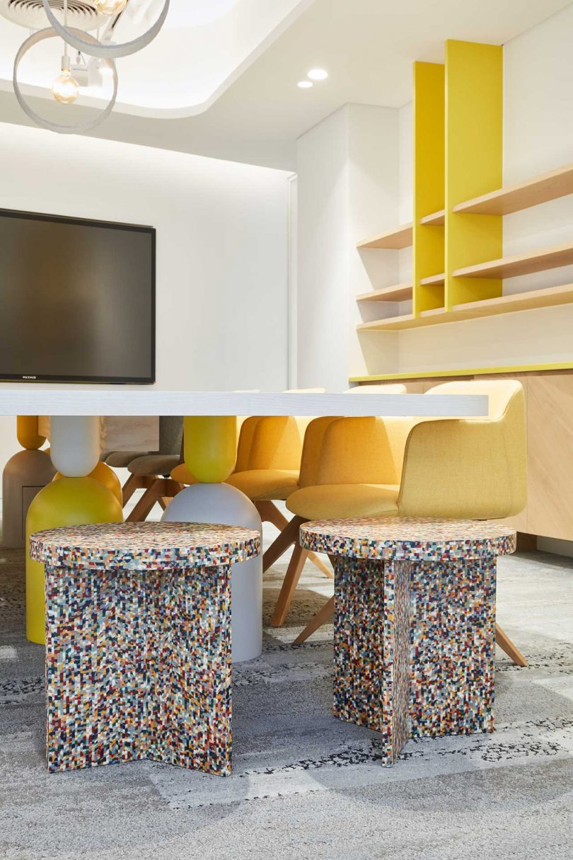 modern white office with yellow shelves and chairs
