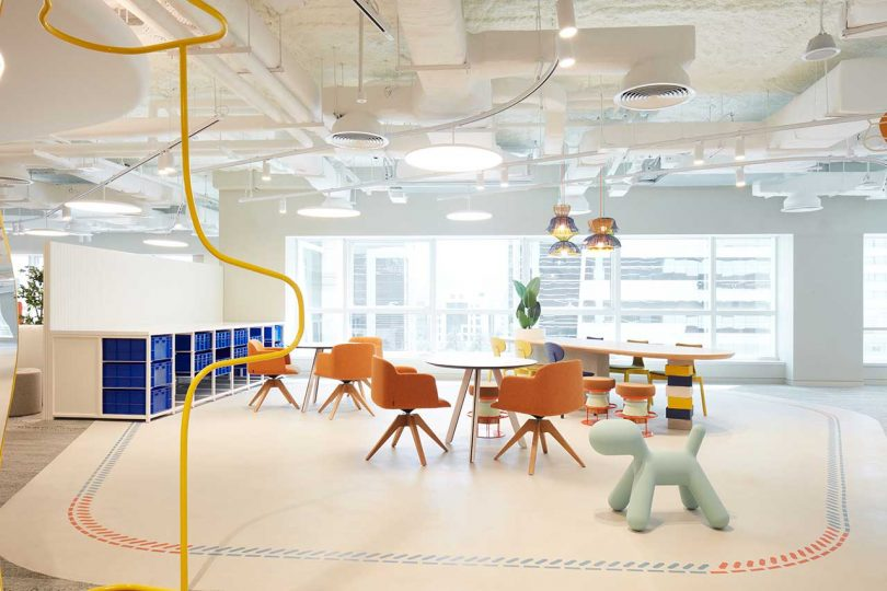 modern white office with orange chairs and white tables