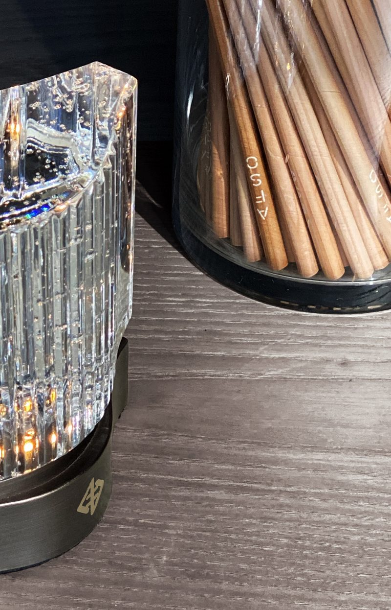 close up of glass container holding pencils and clear beverage in glass