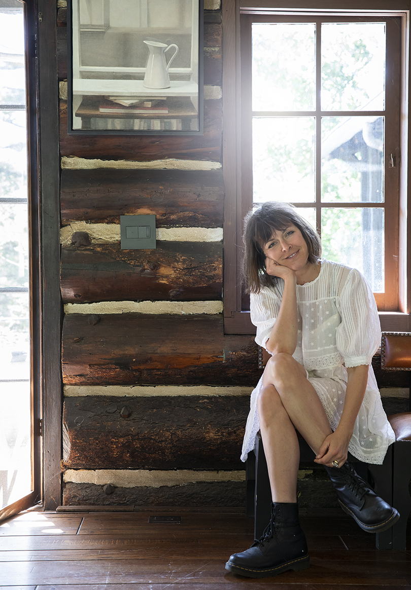 light-skinned woman wearing a white dress and boots sitting on a bench against an interior wall