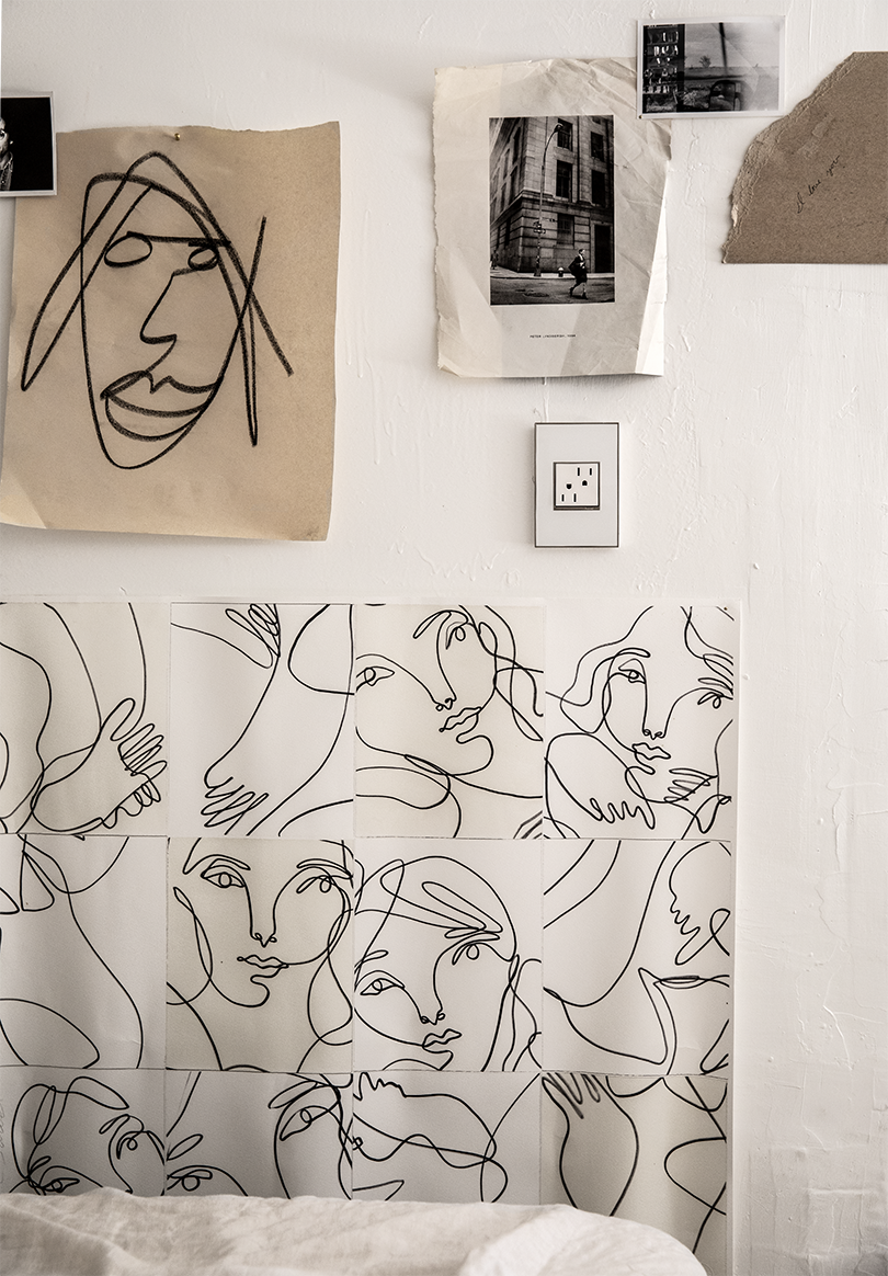 white wall with drawing hanging on it