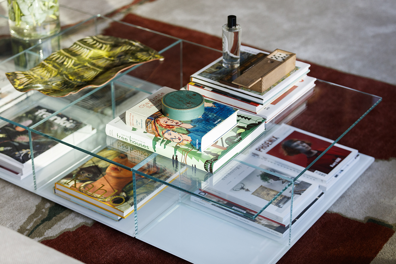 clear coffee table stacked with books