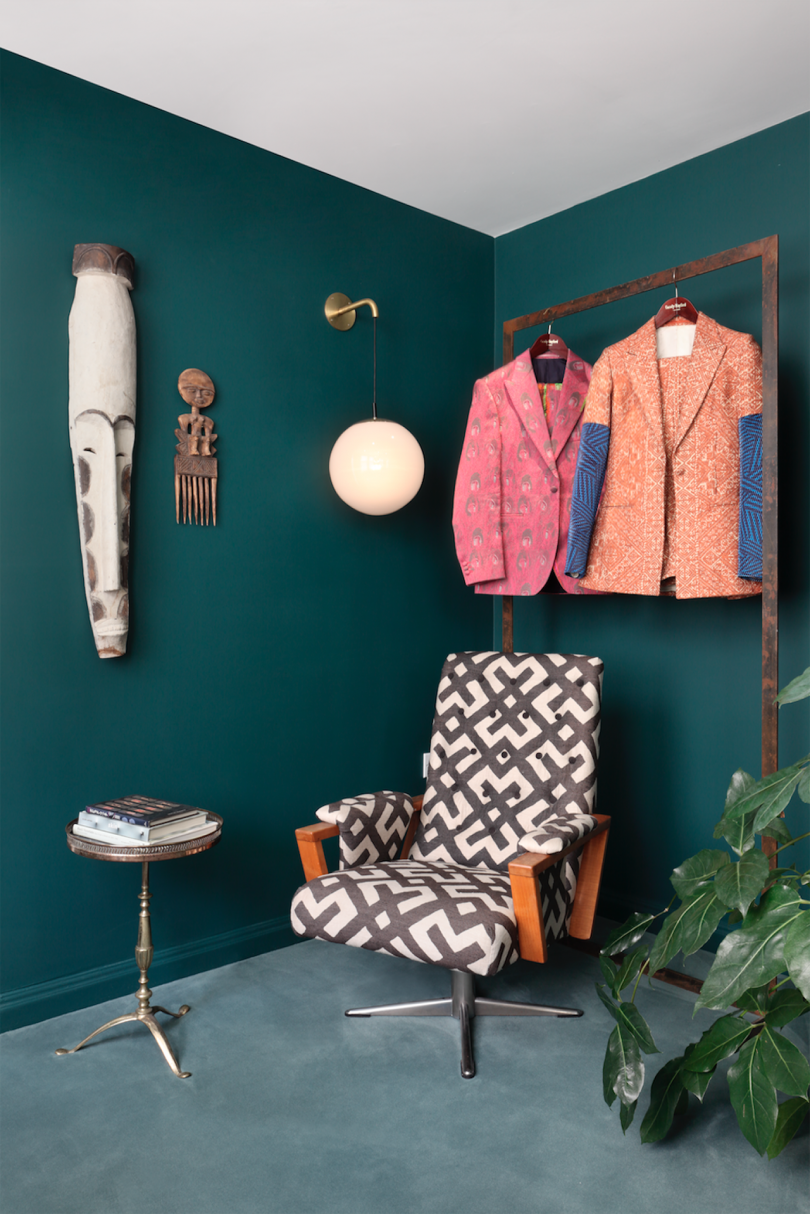 store interior with dark green walls, colorful clothing, and patterned armchair