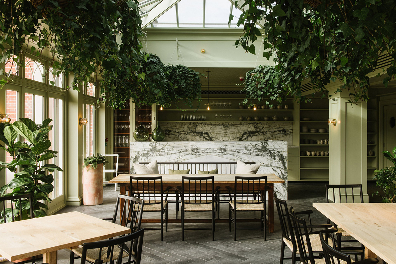 interior dining space with tables, chairs, plants, and high ceiling