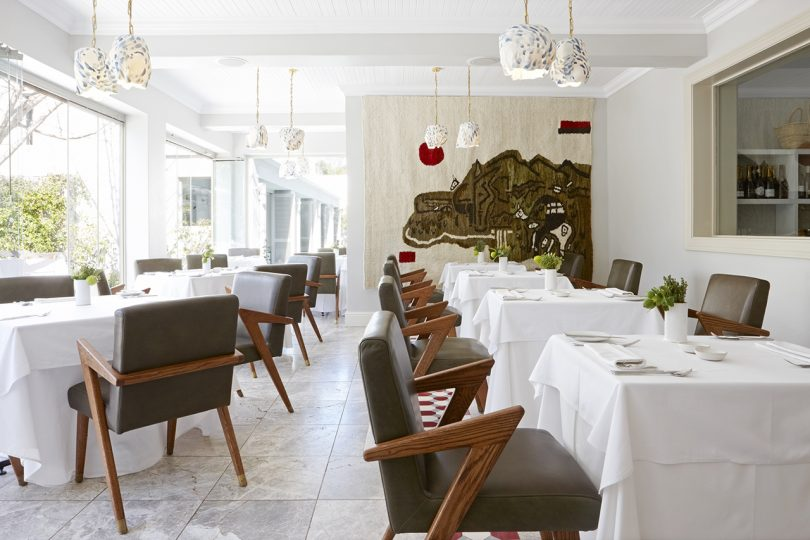 interior dining space with white tablecloth covered tables, armchairs and light walls and floor