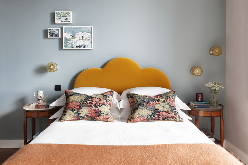 bedroom with curvaceous orange headboard, decorative pillows, and light grey walls