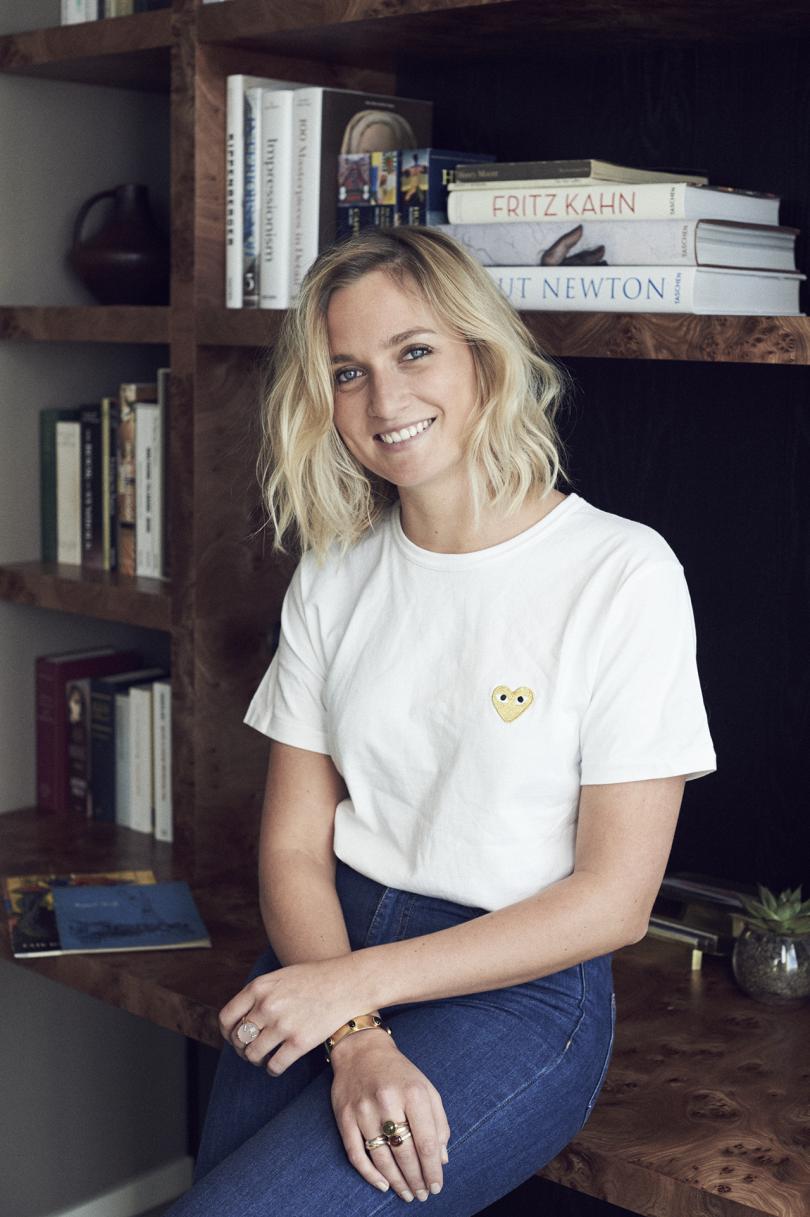 light skinned woman with shoulder length blonde hair posing in front of bookshelves