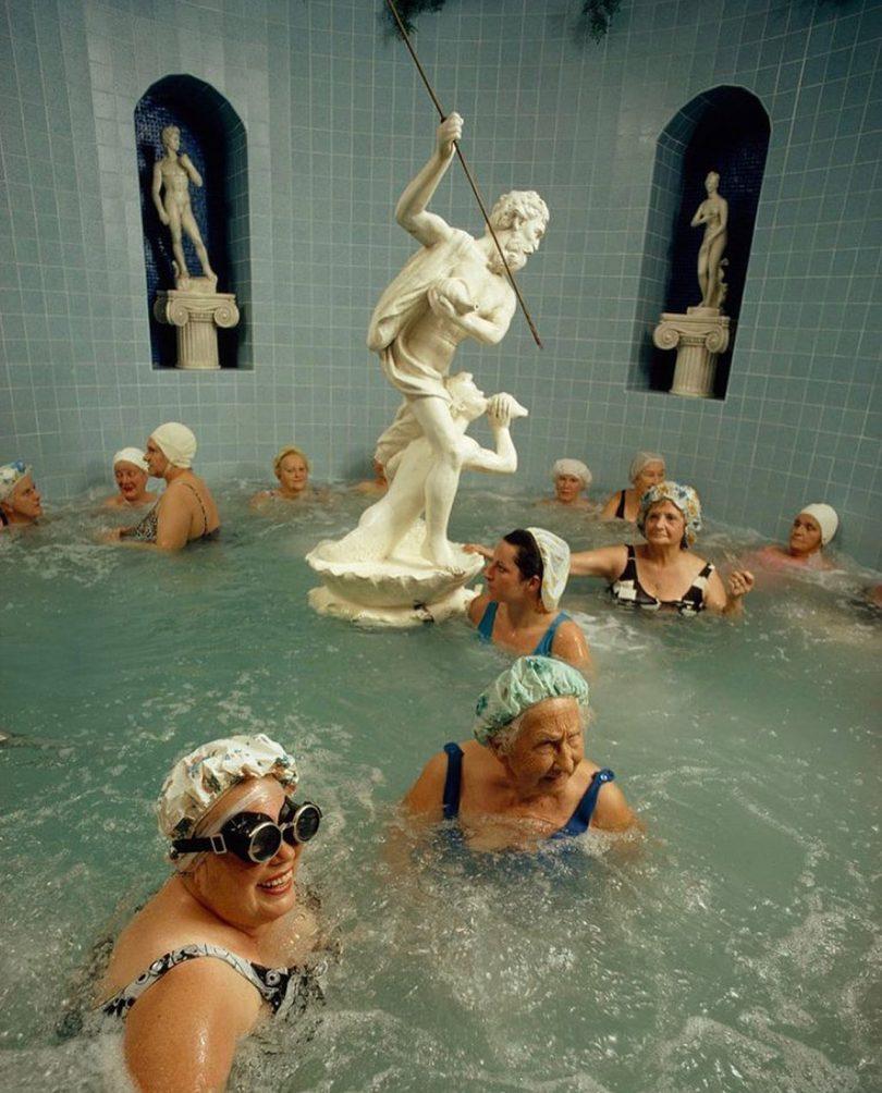 group of older women enjoying an indoor pool with sculptures