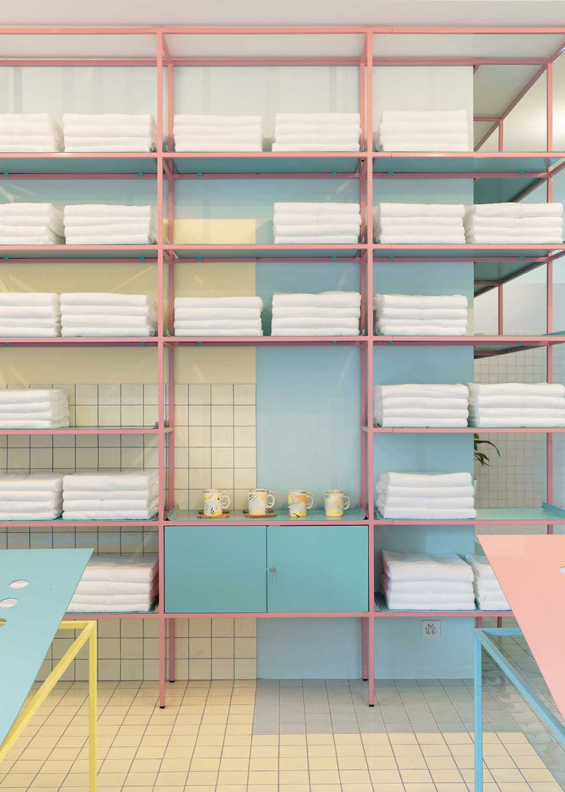 shelving in pastel tiled room with white towels