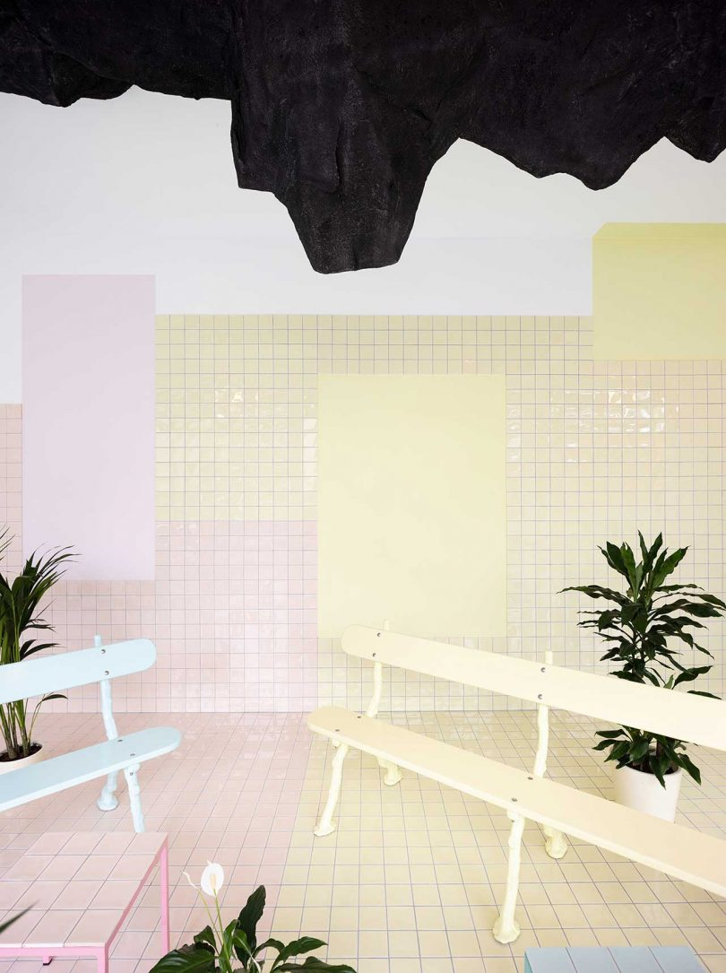 pastel tiled room with benches and plants