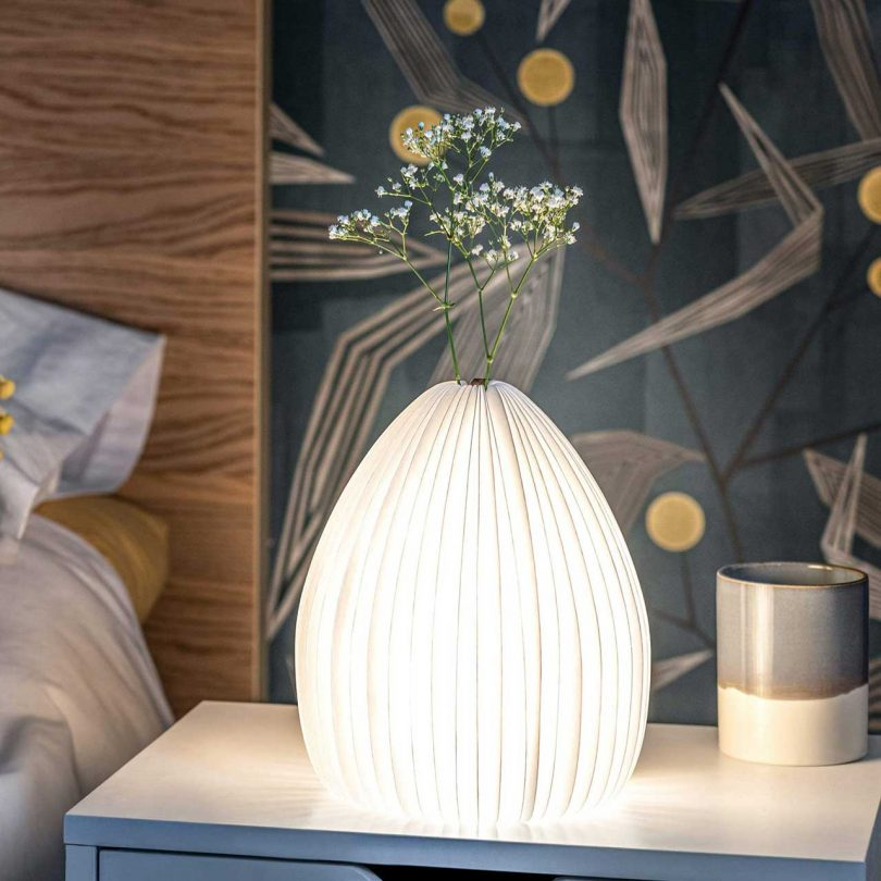 lamp lit with vase holding flower stem