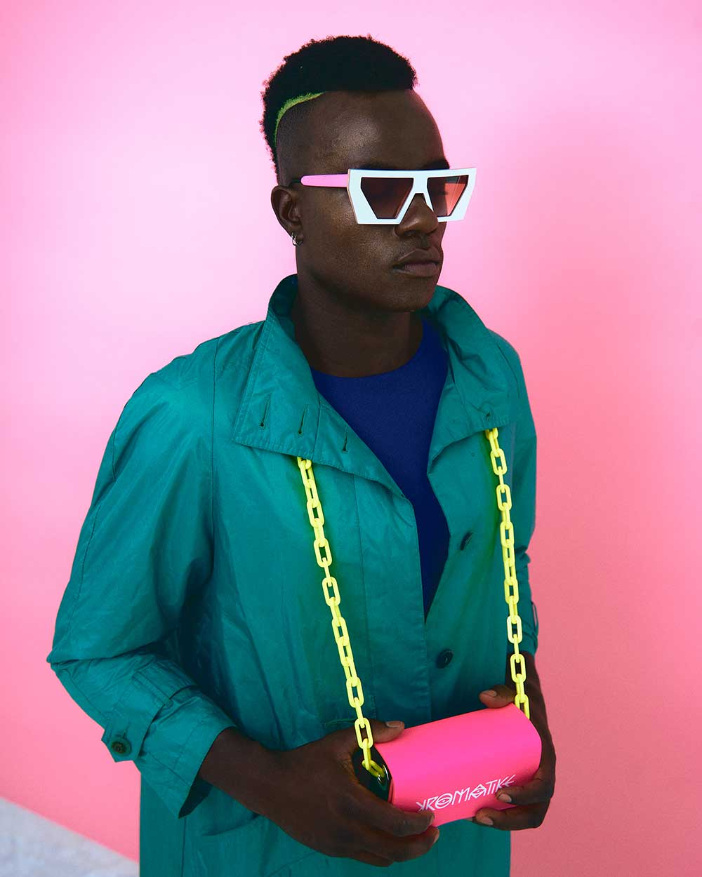 man in green jacket wearing sunglasses and pink bag