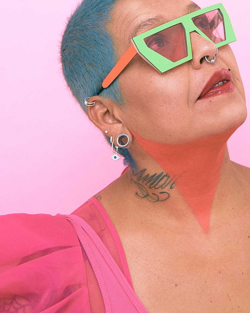 girl with teal hair and green and orange sunglasses