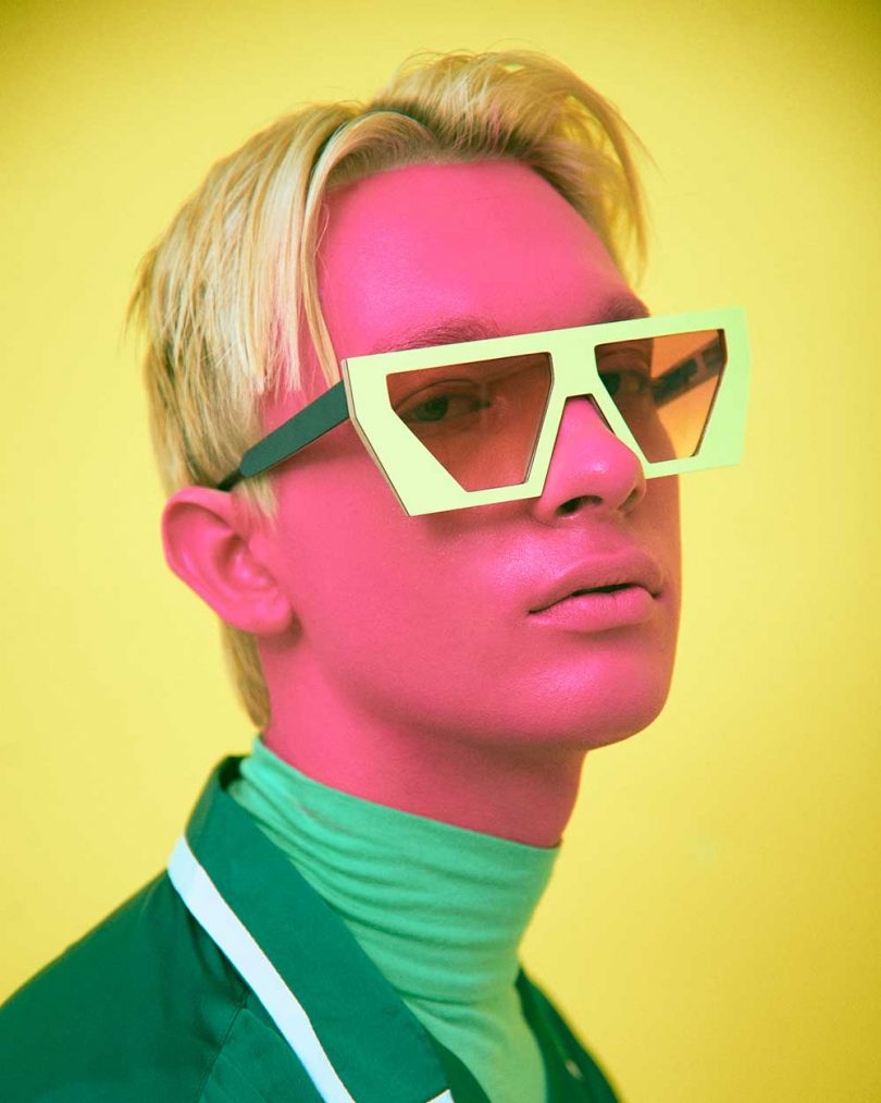 man with pink face and green shirts wearing sunglasses