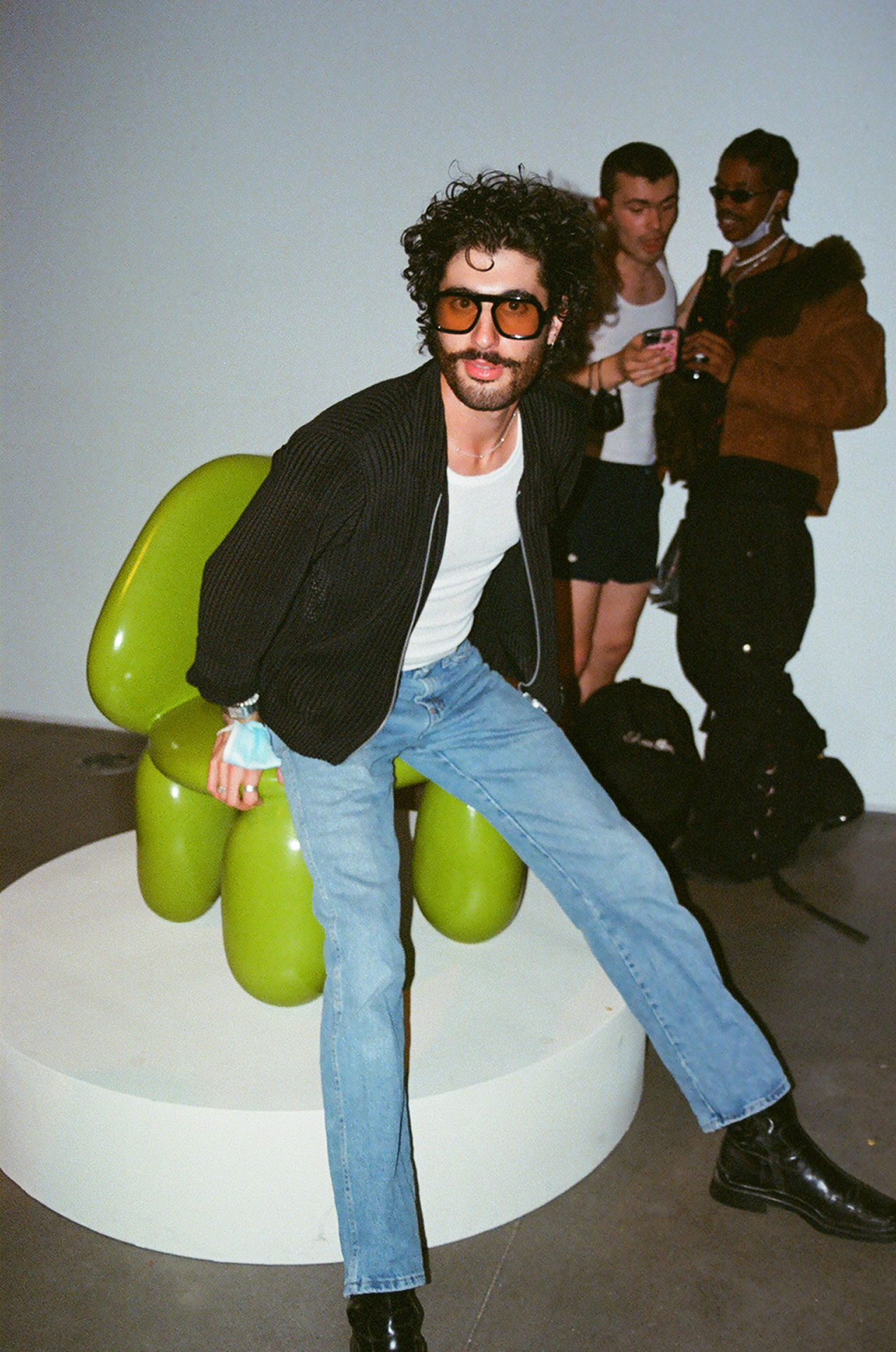 light-skinned man with dark hair wearing a leather jacket, jeans, and sunglasses