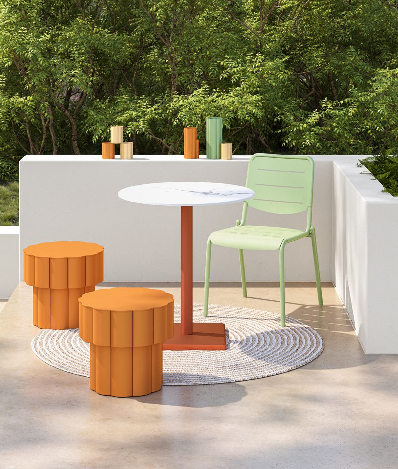 outdoor patio with two orange stools, table, green dining chair, and white wall