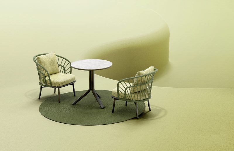 round table with two lounge chairs on light green background