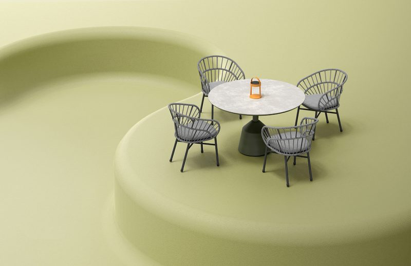 four chairs surround a round table on light green background