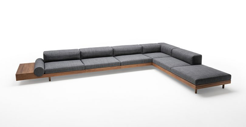 low modular outdoor sofa with wooden frame and grey upholstery on white background