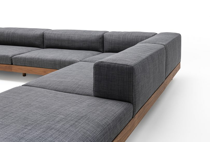 detail of low modular outdoor sofa with wooden frame and grey upholstery on white background