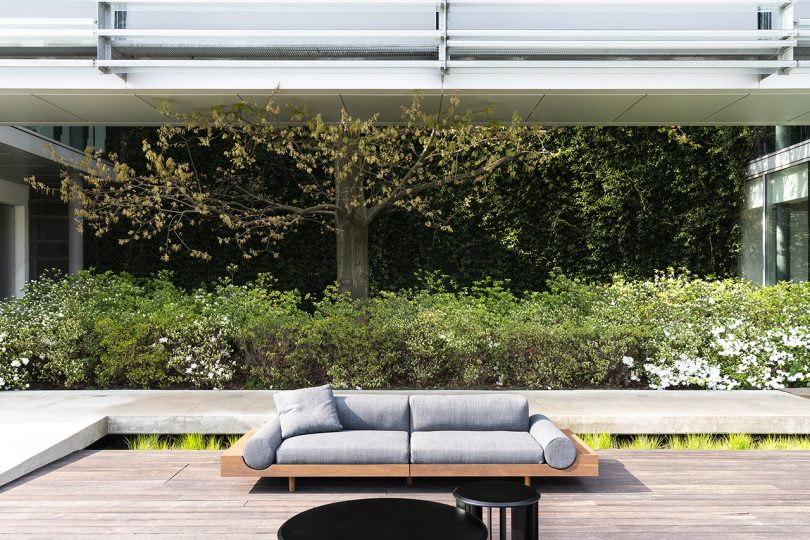low modular outdoor sofa with wooden frame and light grey upholstery on deck with greenery backdrop