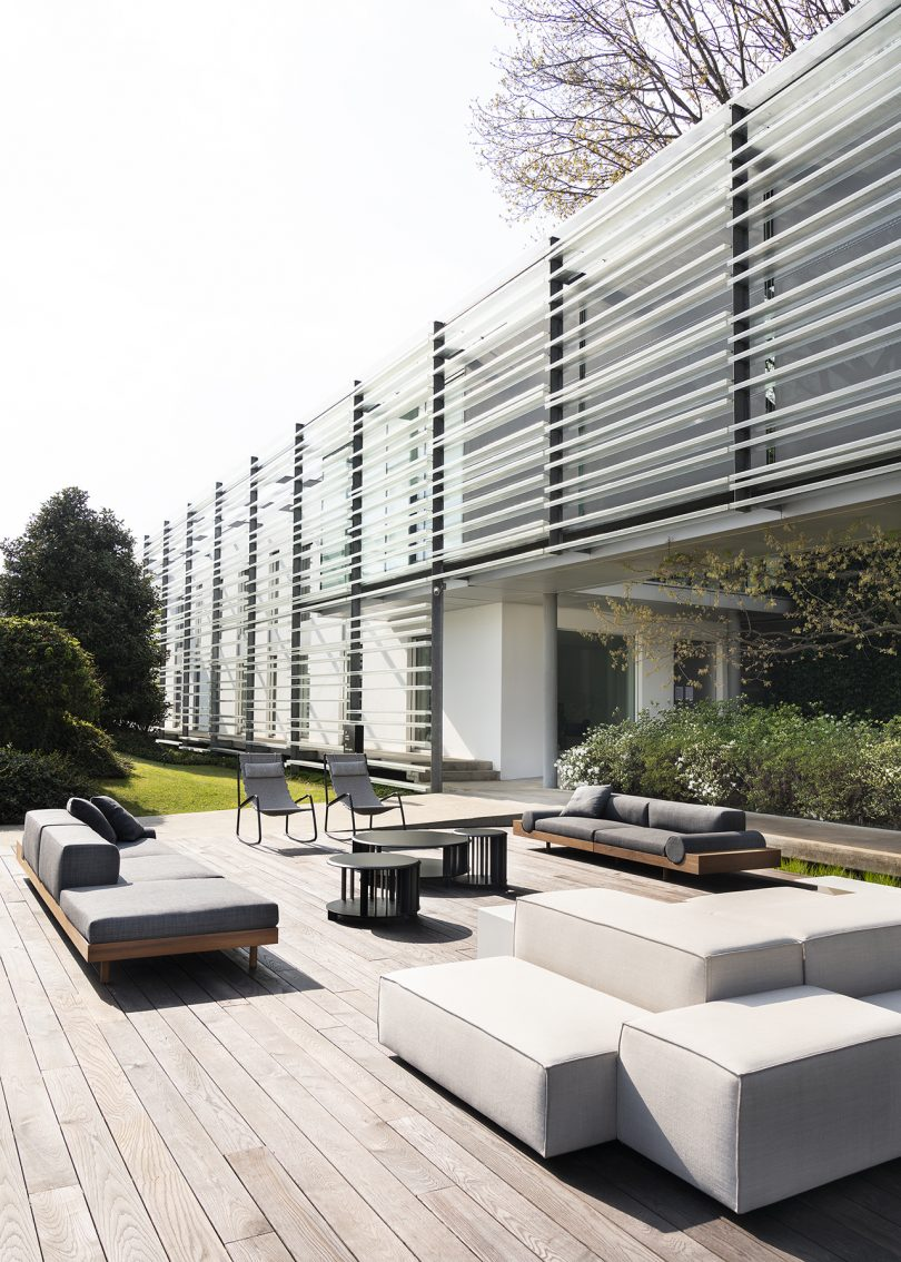 low modular outdoor sofas with wooden frame and light grey upholstery on deck with building backdrop