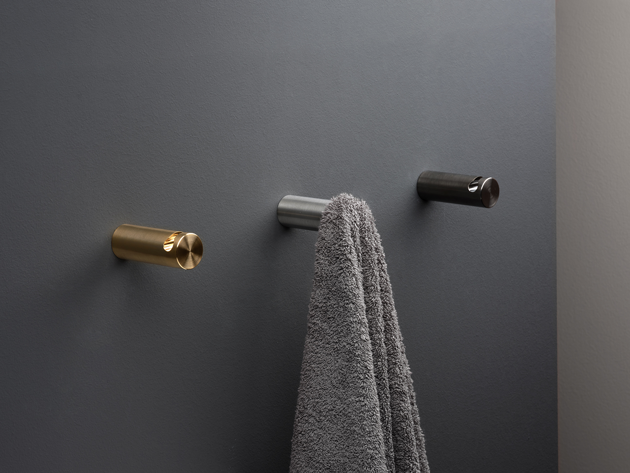 three modern towel hooks mounted to black wall with towel