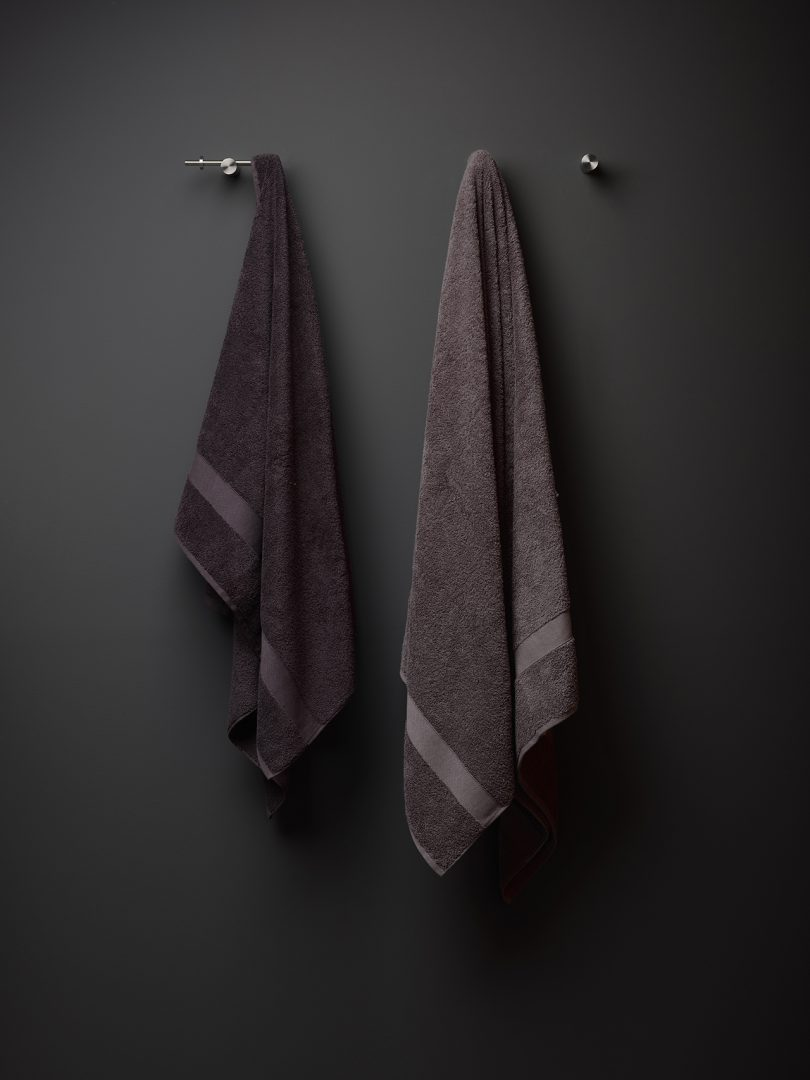 two modern towel hooks mounted to black wall with towels