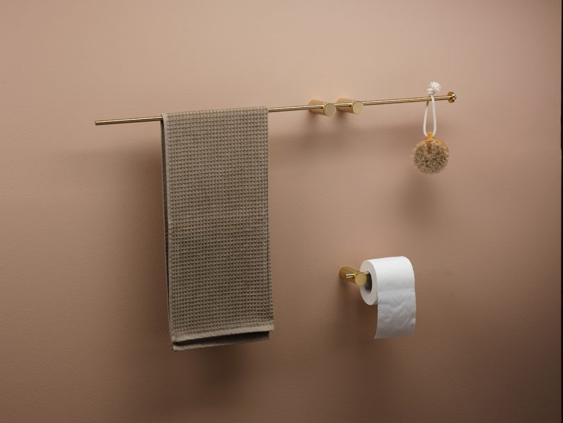 modern bath accessories hanging on on taupe wall