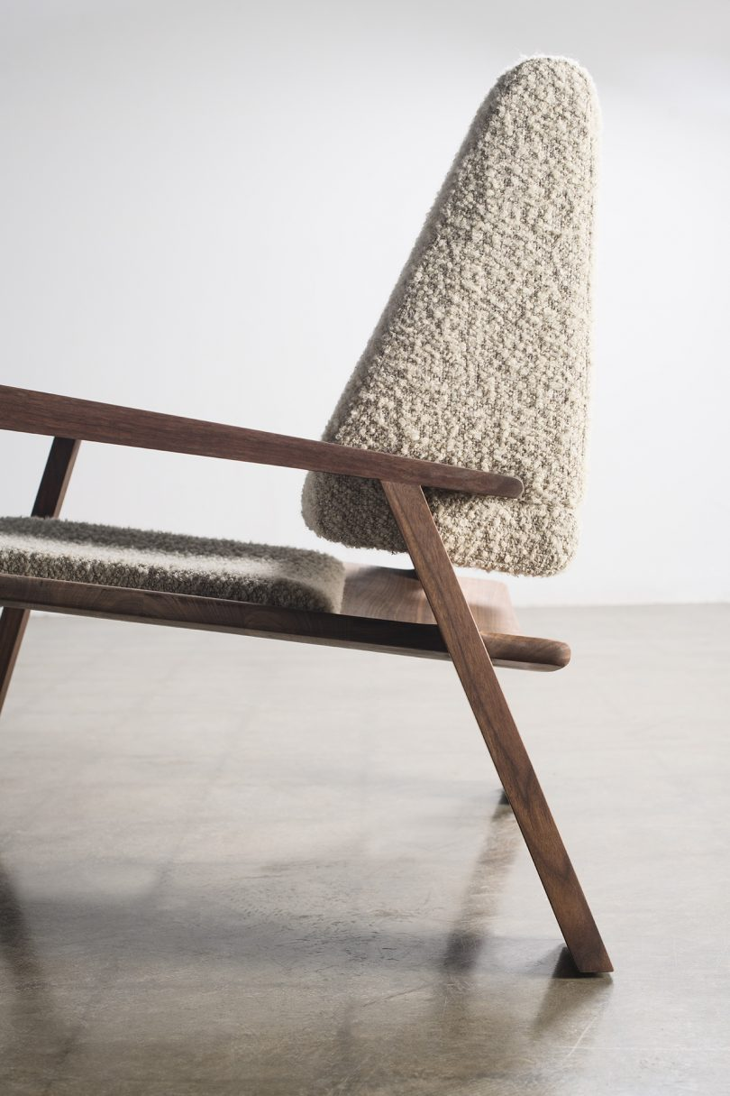 wood and upholstered armchair on cement floor in front of white wall