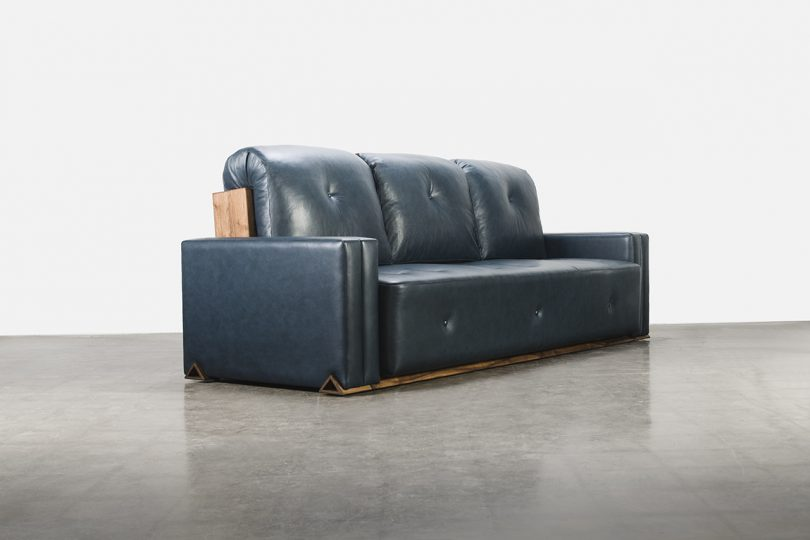 leather and wood sofa on cement floor in front of white wall
