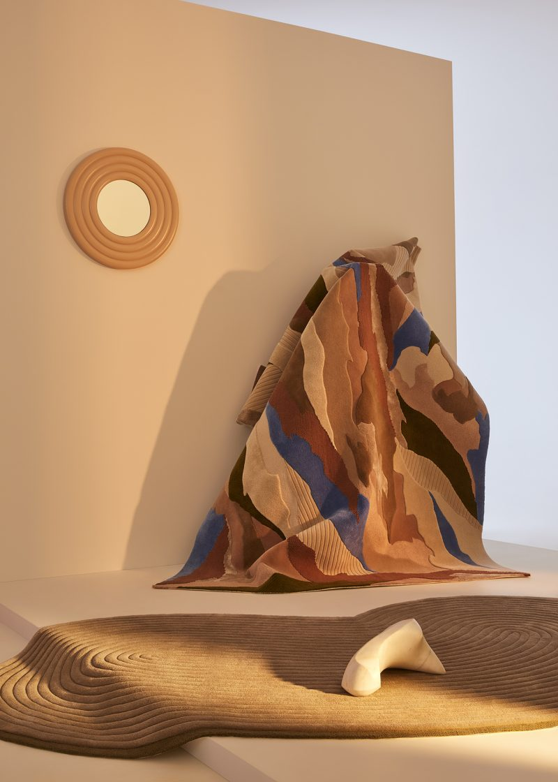 two styled rugs in an indoor space with mirror and soft lighting