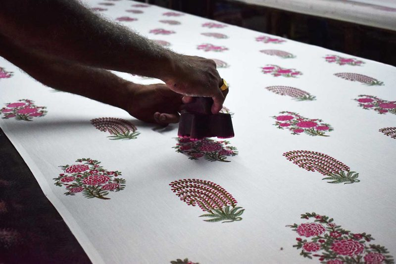 two hands pressing woodblocks onto fabric