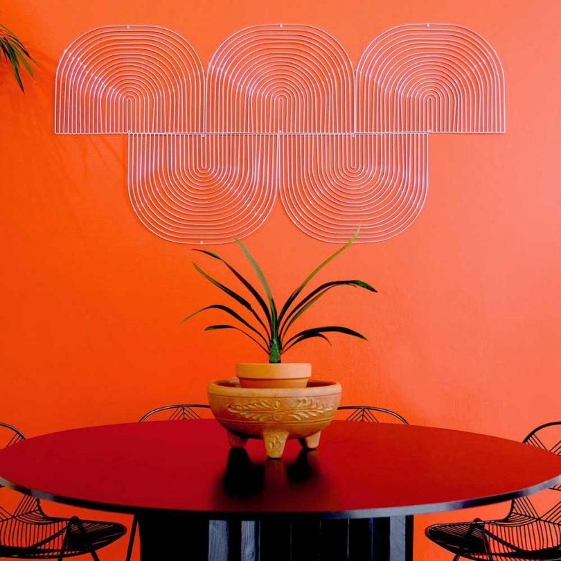 geometric wire wall art on orange wall