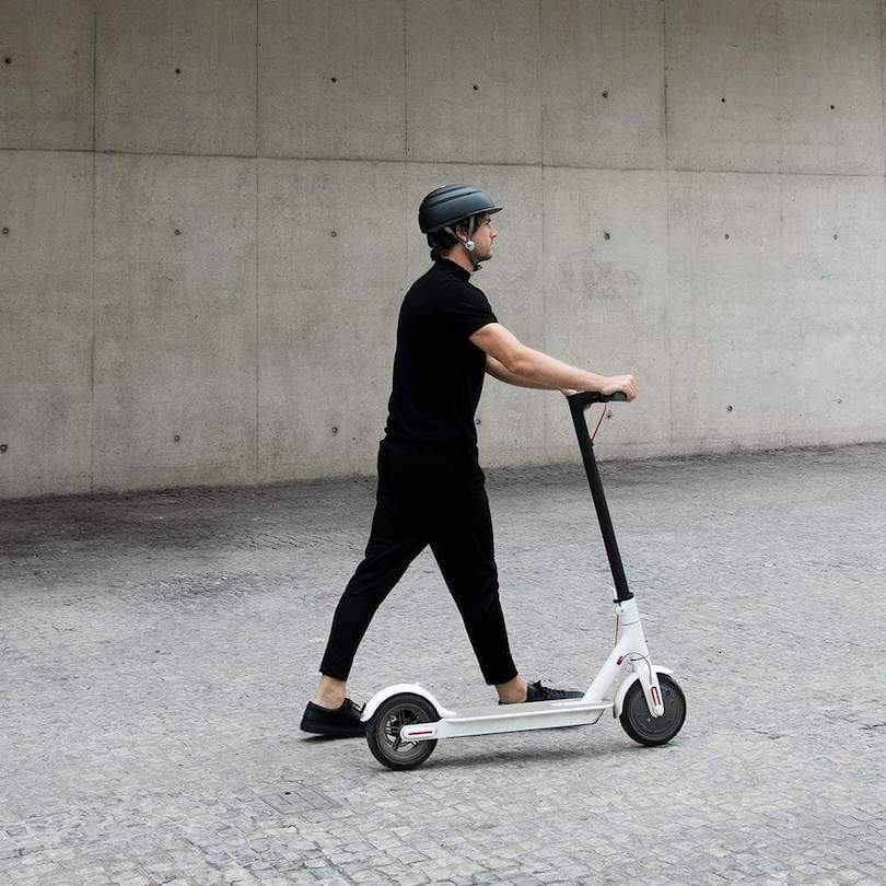 man with safety helmet on walking white scooter