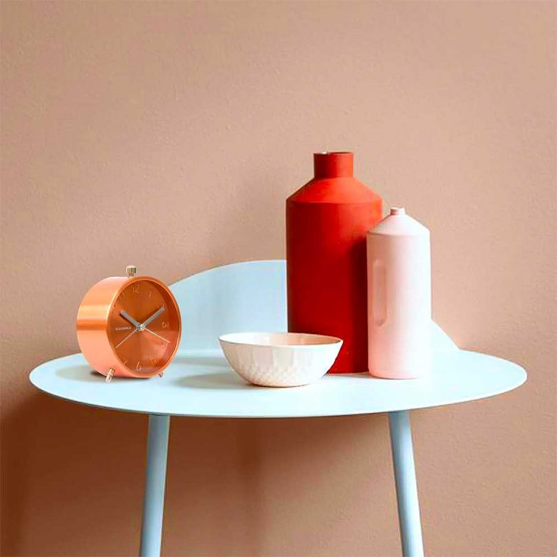 round copper alarm clock on table with vessels