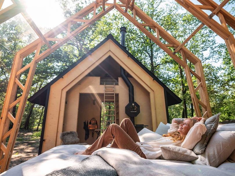 open roof cabin in the woods with girl on bed